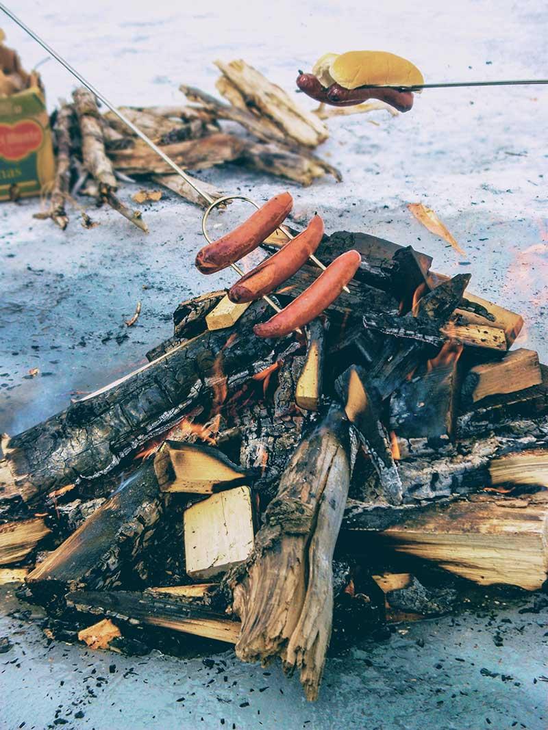 Ice Fishing camp fire with hotdogs and smokies
