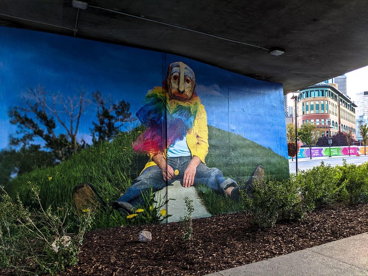 East Village Mask Mural sitting rainbow