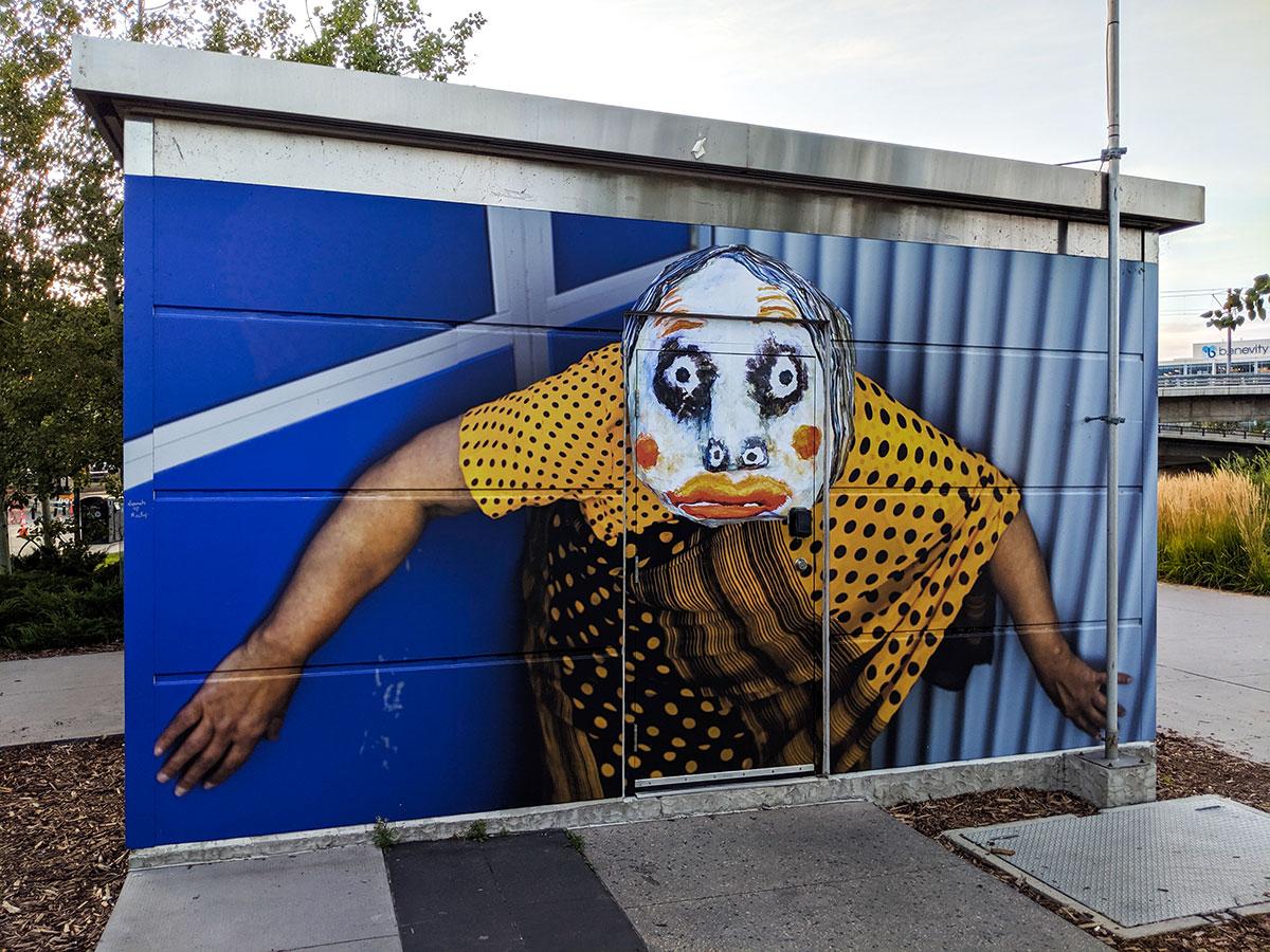 East Village Mask Mural looking at camera