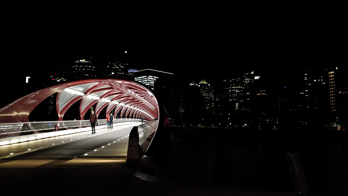 The Peace Bridge in Calgary at night, with the cityscape behind