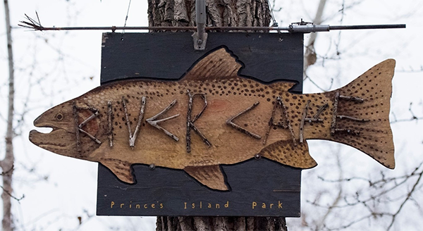 River Café At Prince's Island Park wooden sign shaped like a fish, nailed to a tree